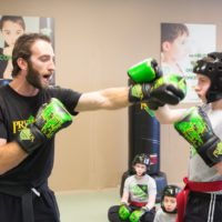instructor and student demonstrate martial arts PMA franchise image